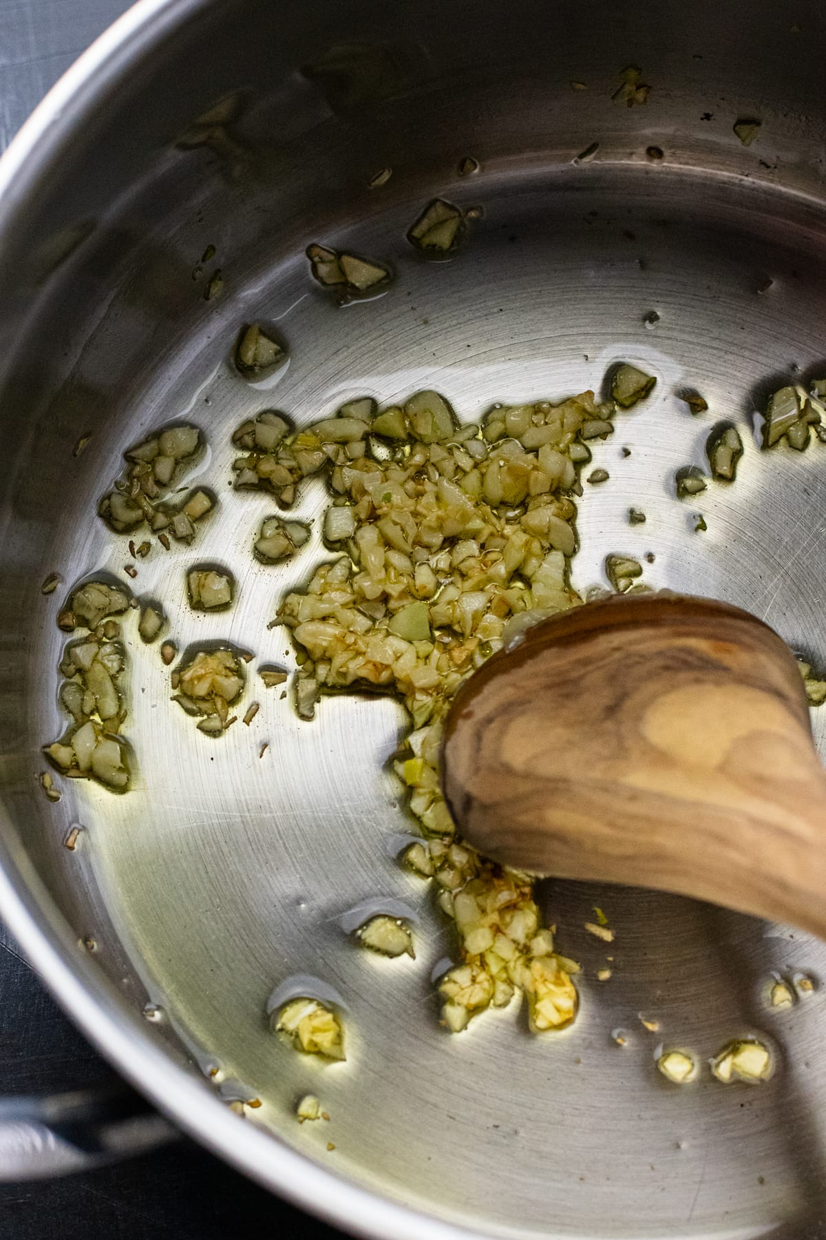 wooden spoon stirring minced garlic in pot with oil.