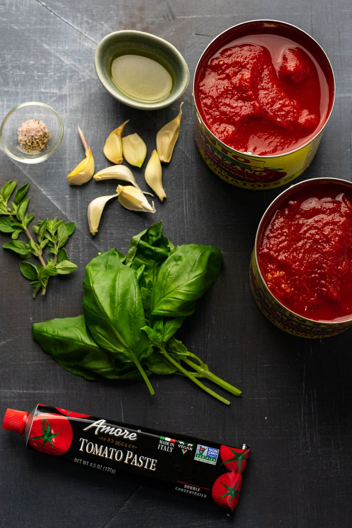 ingredients for tomato sauce arranged on gray background.