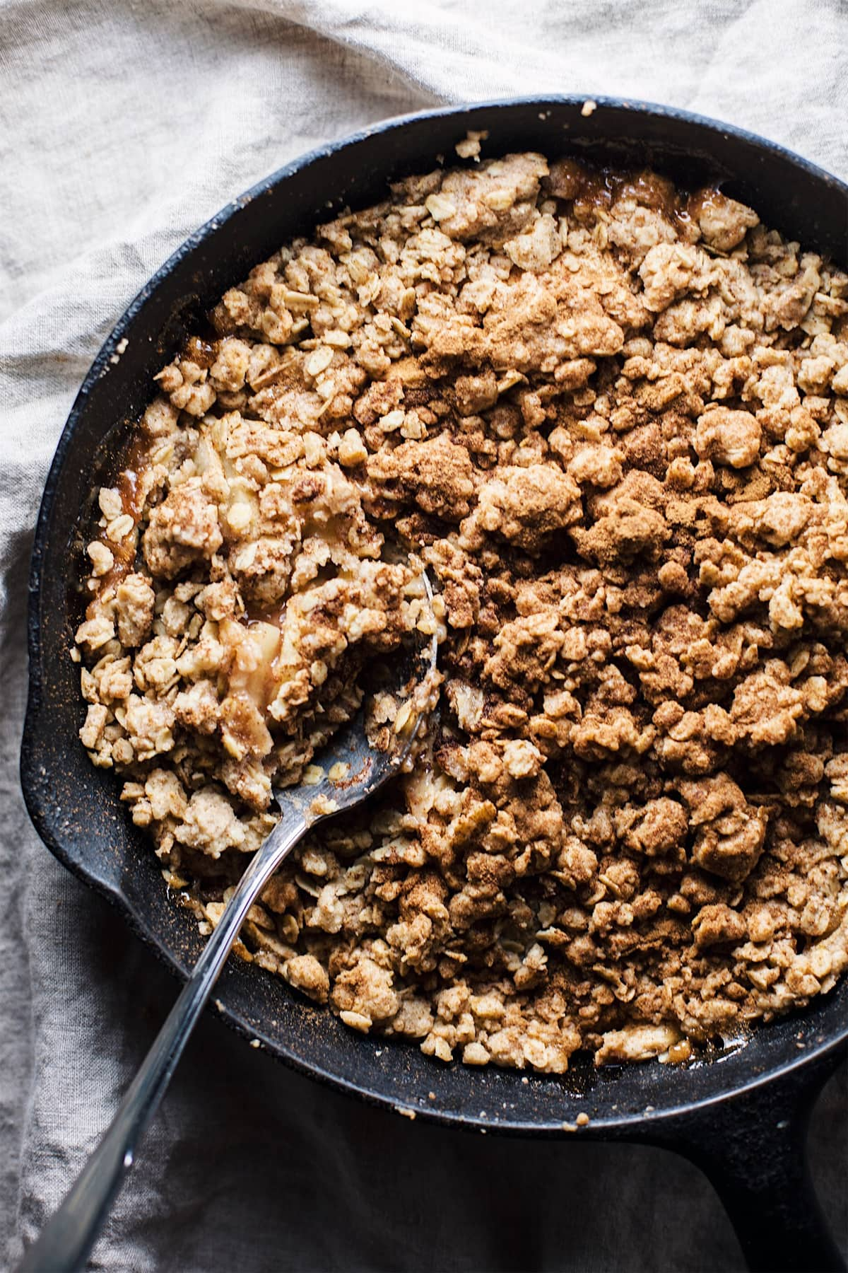 Cast iron skillet of apple crumble with a spoon in it.