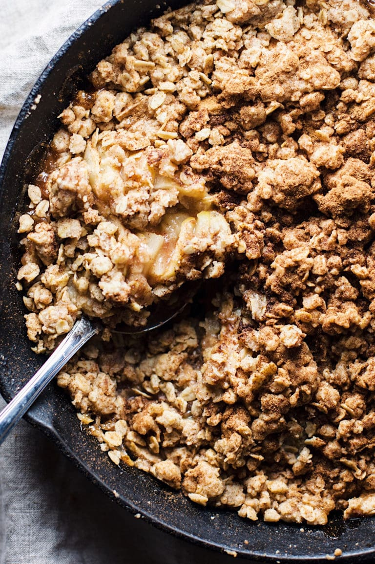 a close up of apple crumble with a spoon in it.