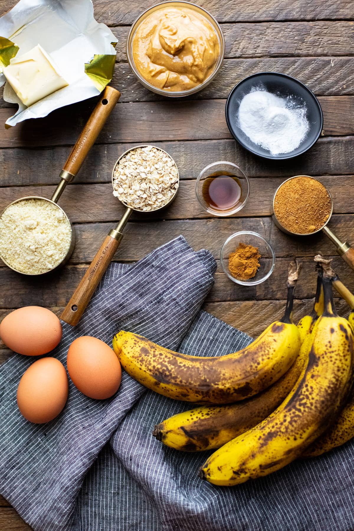 Ingredients for flourless banana bread arranged on brown wooden board.