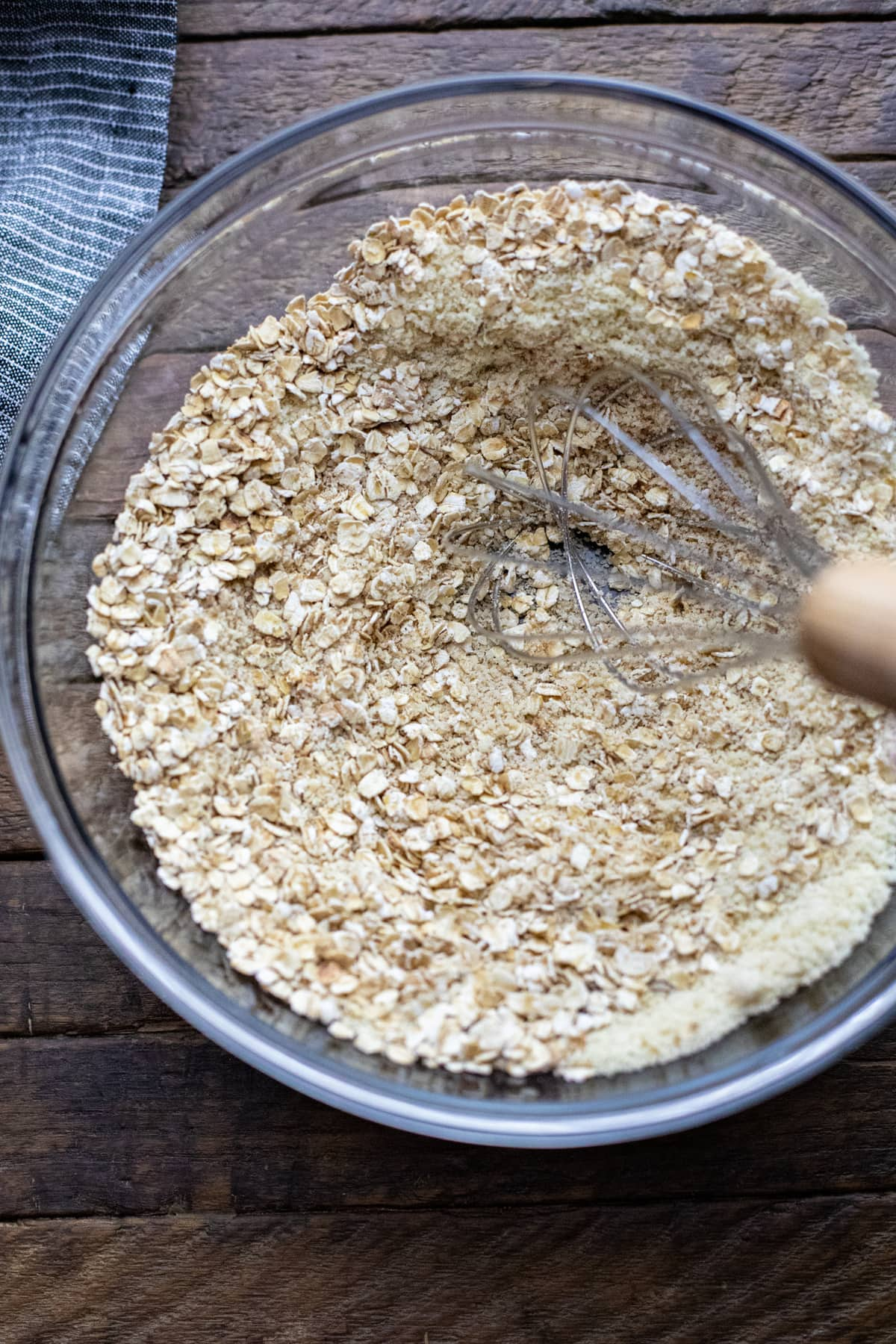 dry ingredients being whisked in a clear glass bowl.