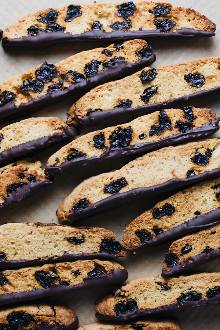 Italian biscotti dipped in dark chocolate laid on parchment paper.