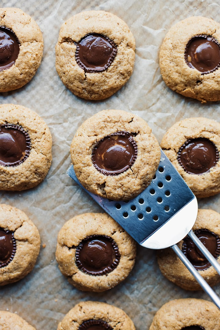 A spatula lifting peanut butter cup cookies on parchment paper