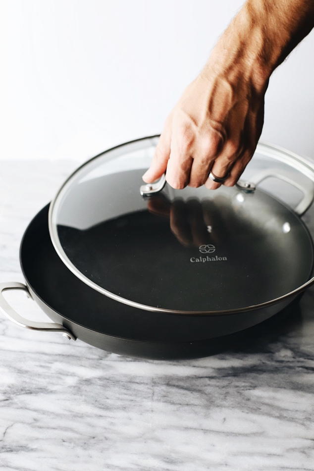 A hand picking up the lid on a calphalon pot