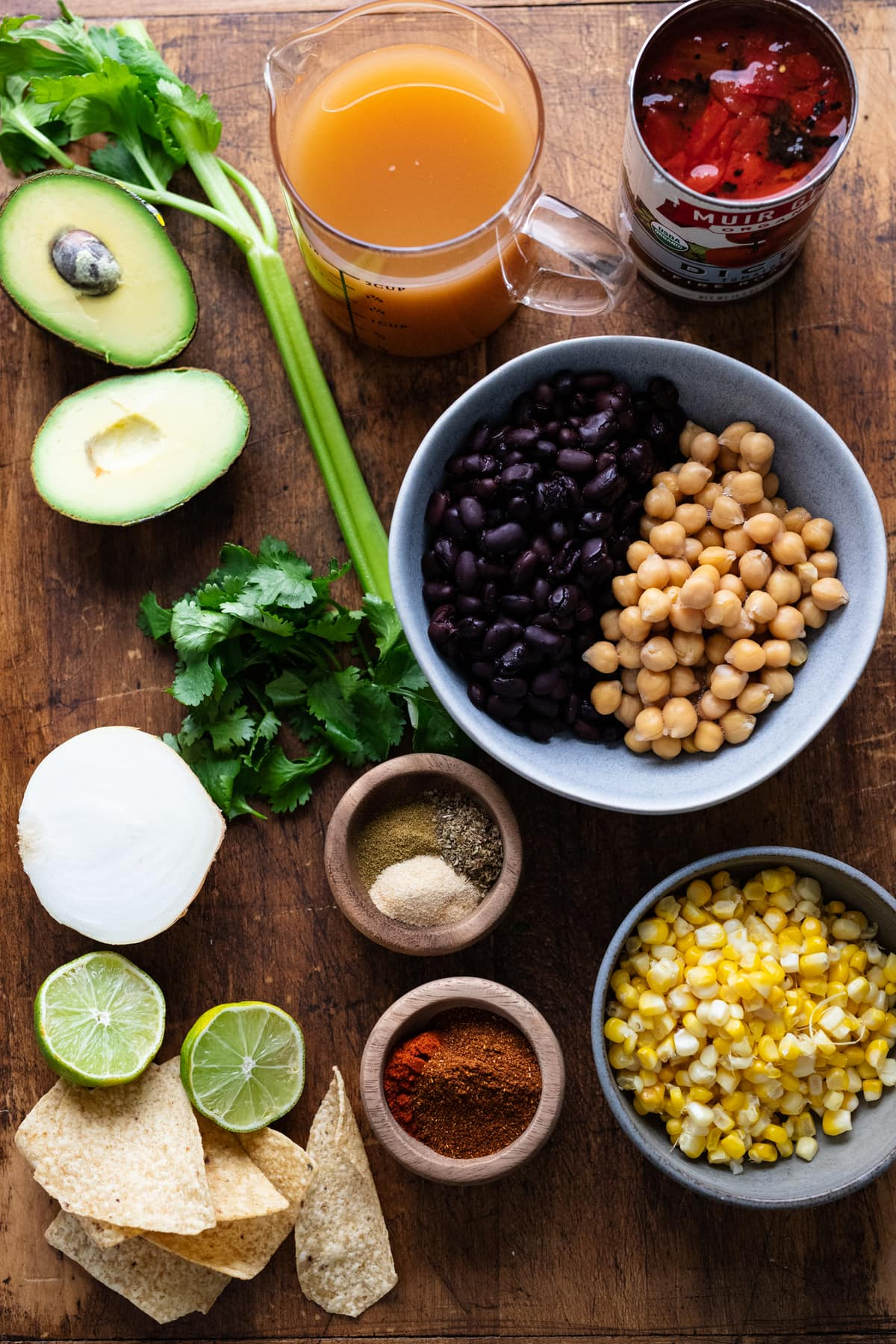 Ingredients for vegetarian tortilla soup arranged on a wooden background.