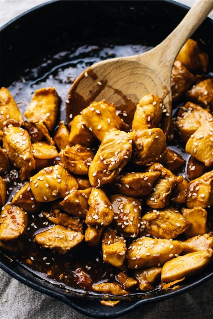 A wooden spoon stirring teriyaki chicken in a black cast iron skillet