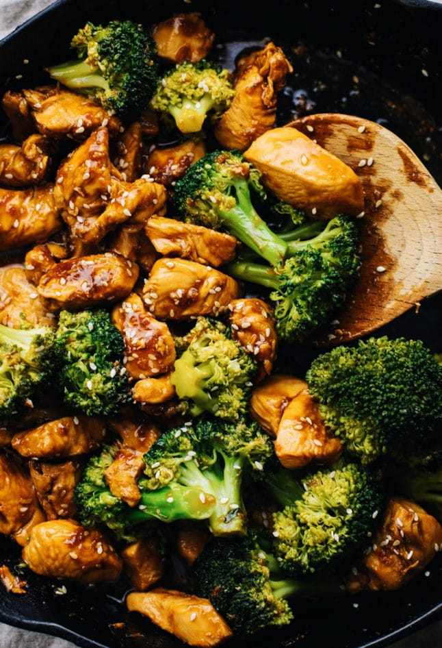 A close up of teriyaki chicken in broccoli in a cast iron skillet with a wooden spoon.