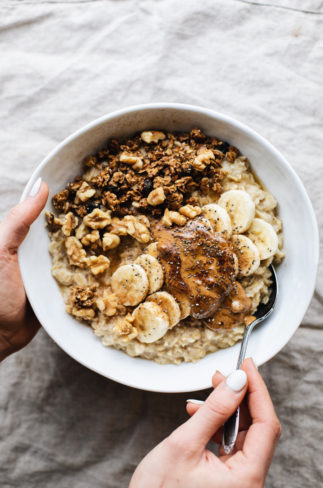 A white bowl of banana oatmeal on a grey napkin with granola and walnuts sprinkled on top.