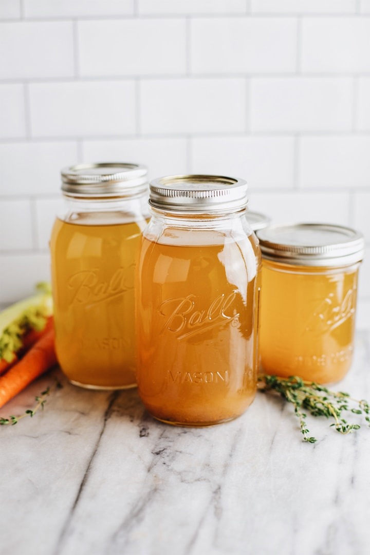 Mason jars of homemade vegetable broth against a white background.