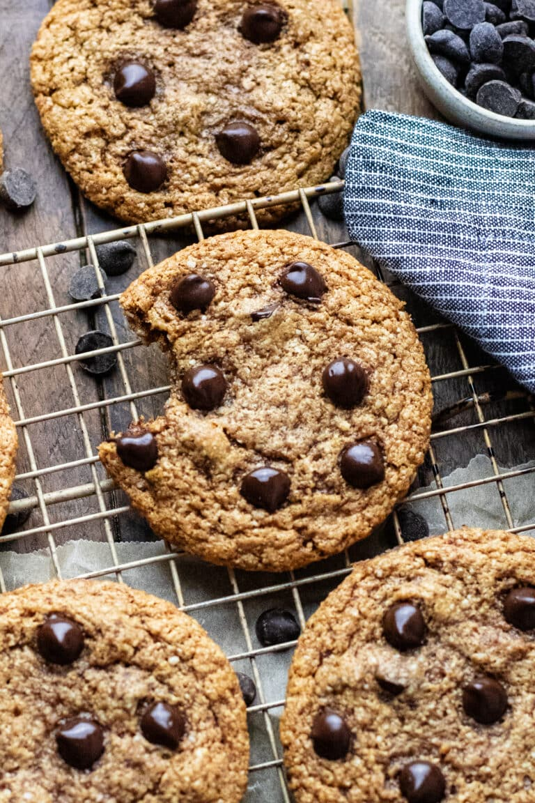 almond butter chocolate chip cookies arranged on a cooling wrack on brown wooden board.