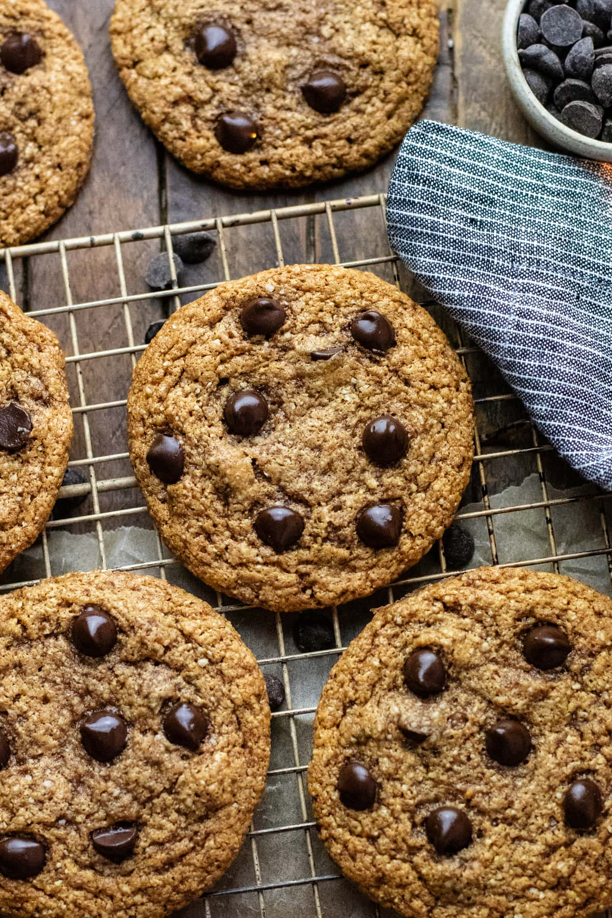 chocolate chip almond nutter cookies arranged on cooling wrack with dark blue napkin next to it.