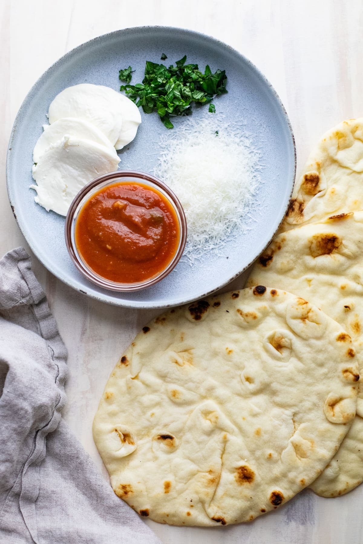 Ingredients for naan pizza arranged on a plate with naan bread next to it.