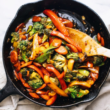 A black cast iron skillet with assorted vegetable stir fry and a wooden spoon in it.