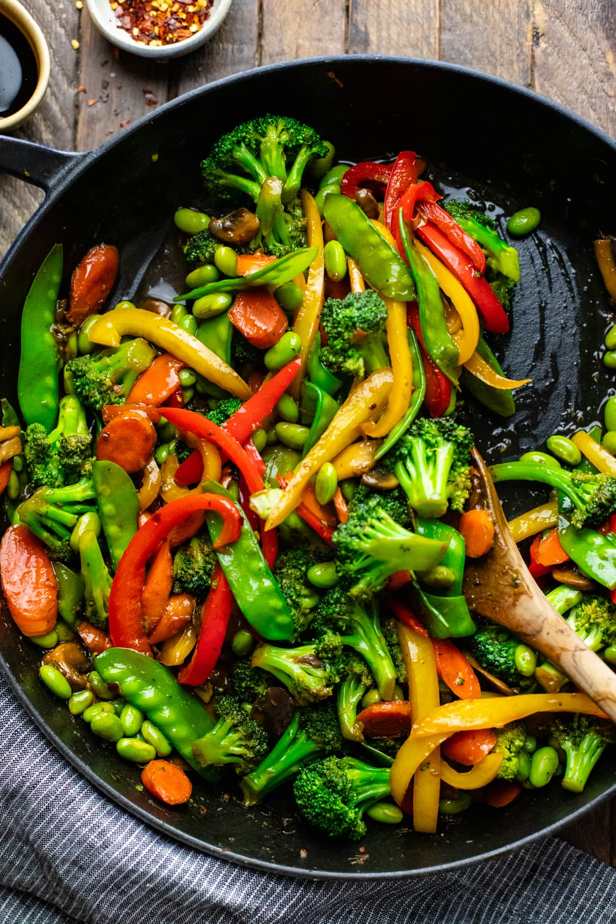 spoon mixing stir fry vegetables in cast iron pan on brown wooden board.