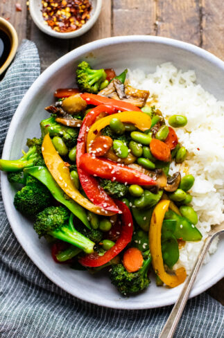 vegetable stir fry with white rice in white ceramic bowl with dark napkin next to it.