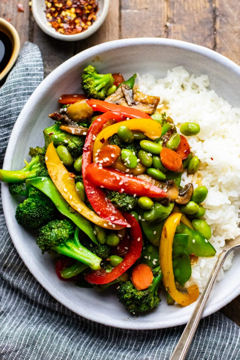 vegetable stir fry with white rice in white ceramic bowl with dark napkin next to it.
