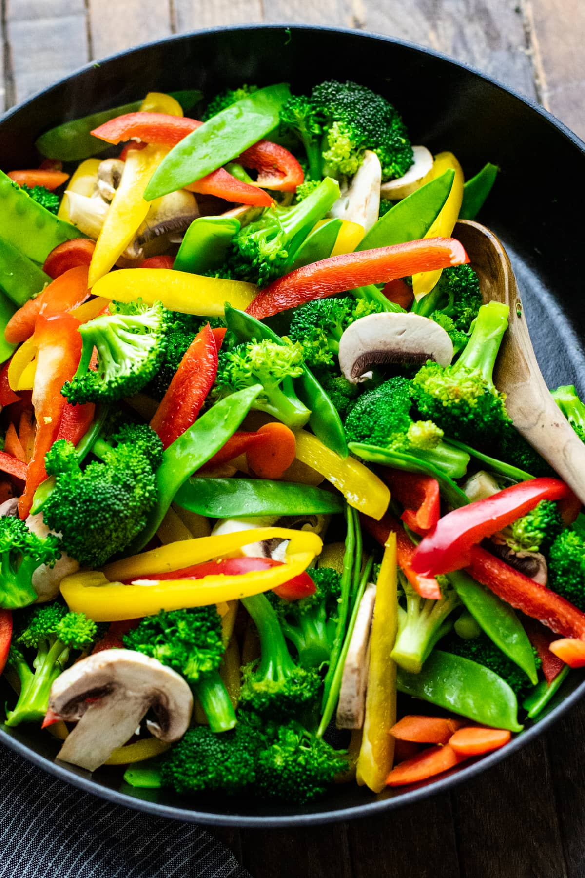 wooden spoon stirring vegetables in black cast iron pan.