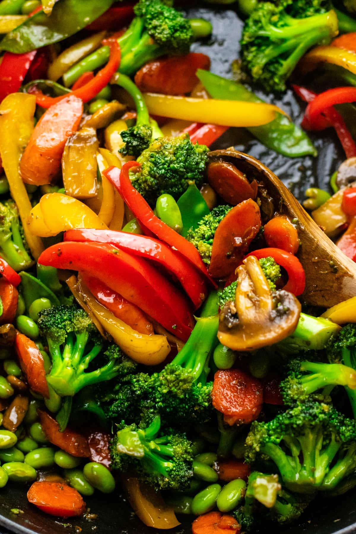 spoon stirring vegetable stir fry in a pan.