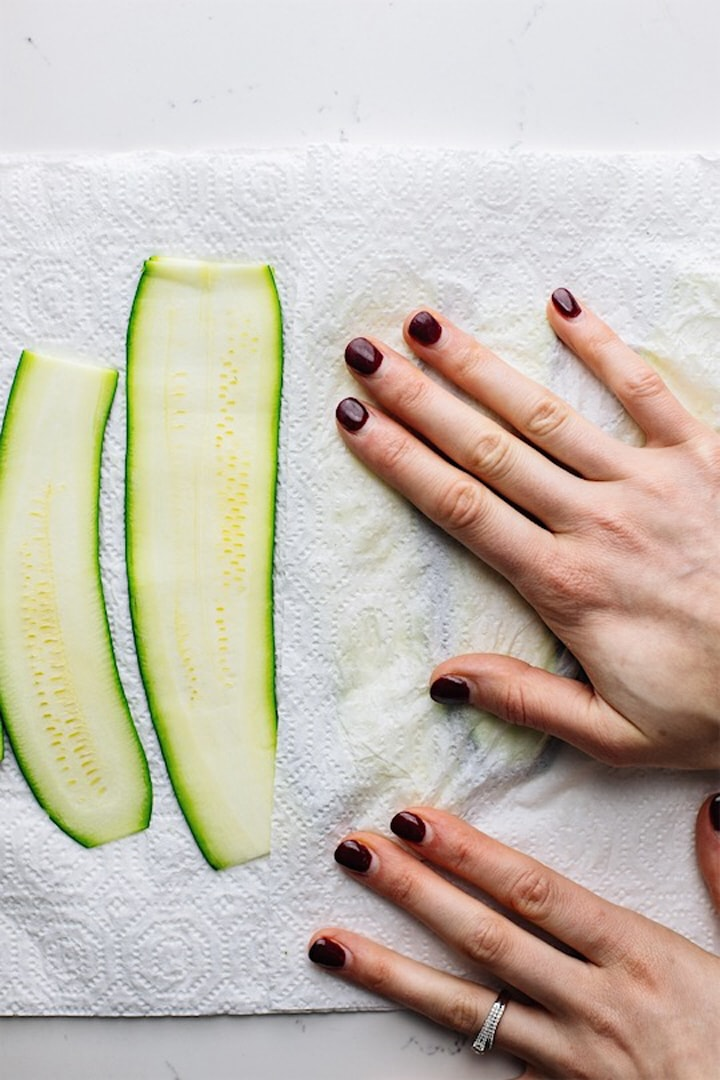 A hand patting dry zucchini noodles on paper towels.