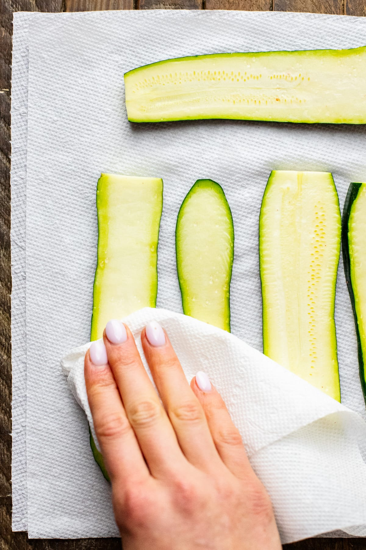 hand patting dry zucchini slices with paper towel.