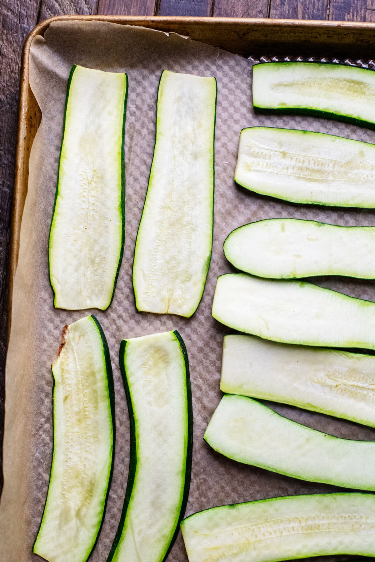 zucchini sliced thin and arranged on baking sheet lined with parchment paper.