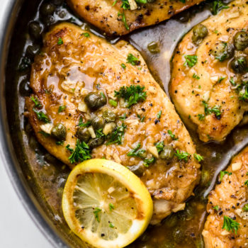 A close up of lemon chicken piccata in a pan with lemon slices and chopped parsley.