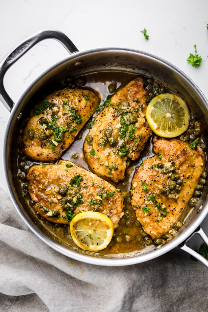 a silver pan on a white background with lemon chicken piccata and lemon slices over top.