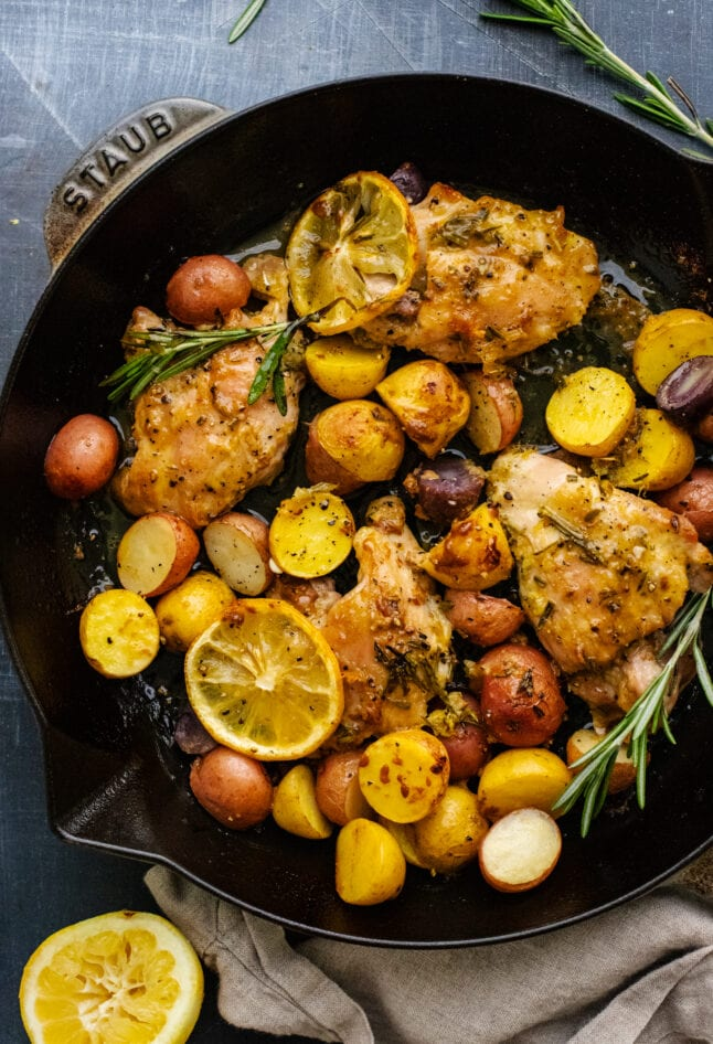 black skillet pan with lemon rosemary chicken and baby potatoes in it.