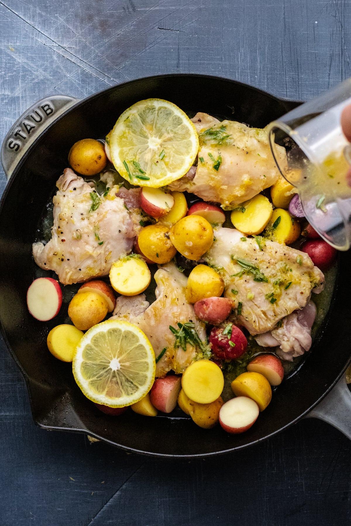 glass jar pouring sauce over lemon rosemary chicken in black skillet pan.