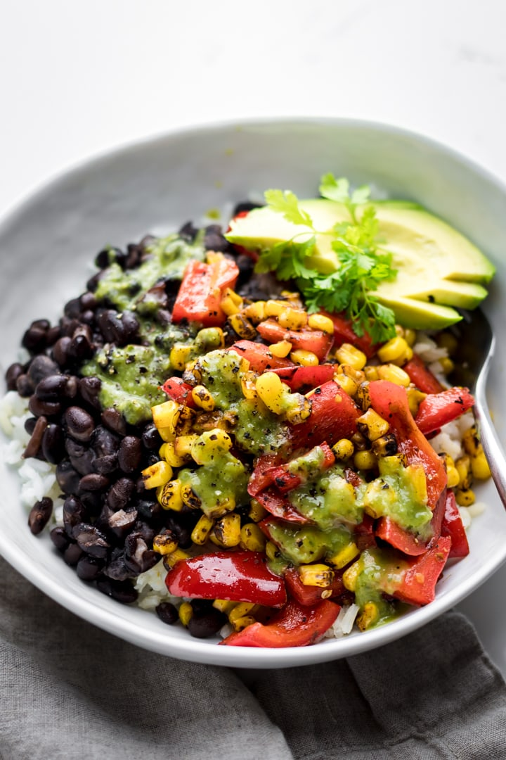 close up of corn, peppers, and black beans in a while bowl.
