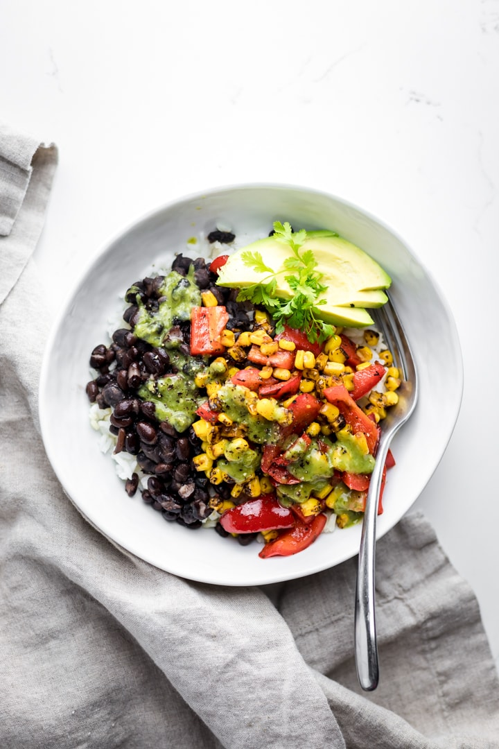 A white bowl of vegan burrito bowl on a white background with a gray napkin.