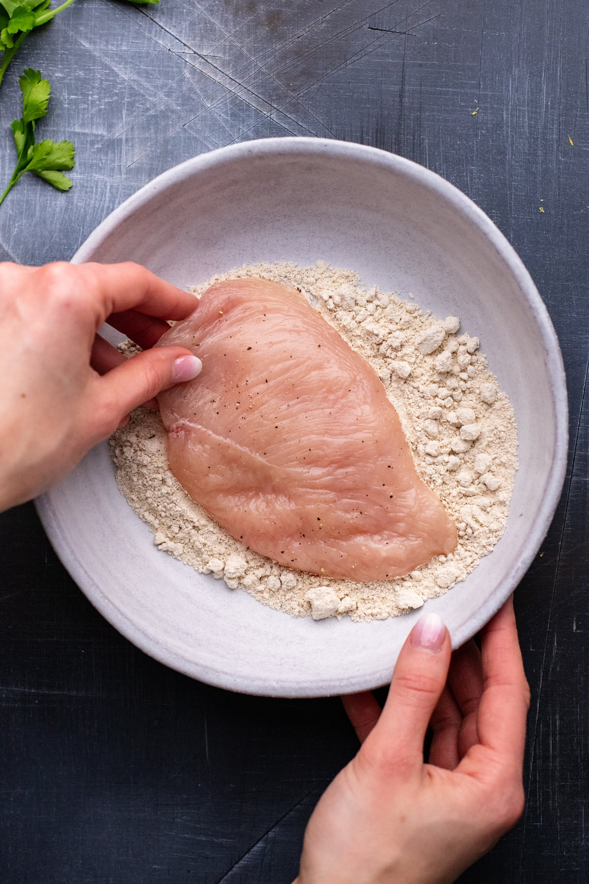 hand dipping chicken breast into white bowl of flour on gray background.