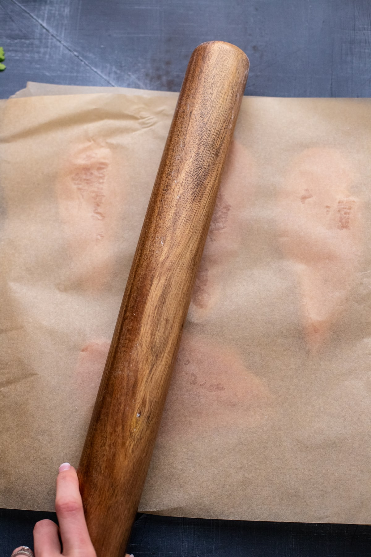 hand using rolling pin to pound chicken in between parchment paper.