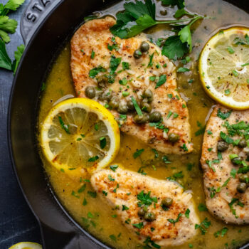 close up on slice of chicken piccata in sauce with lemon slices and fresh parsley leaves.