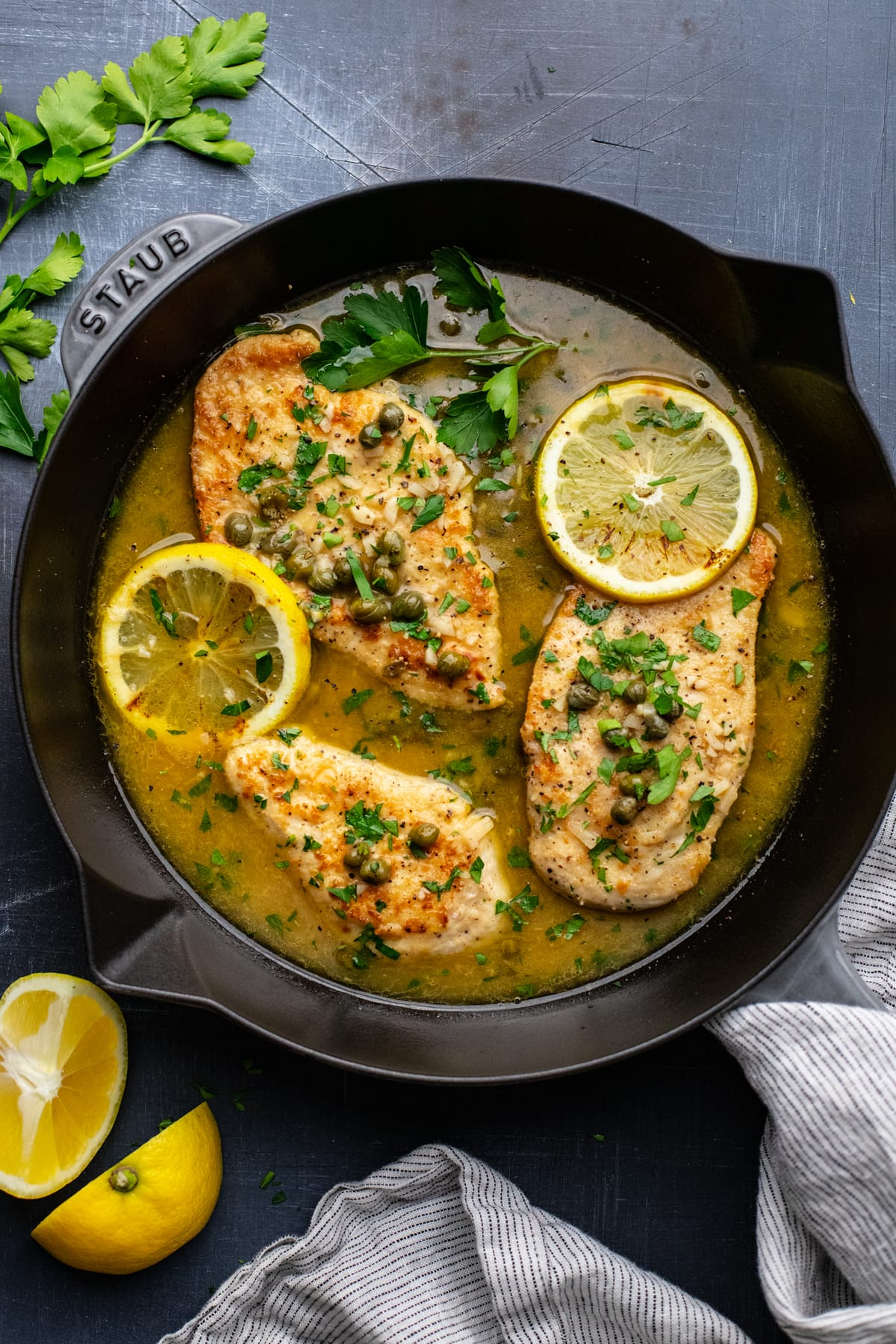 skillet pan with lemon chicken piccata in it on gray background with lemon slices and fresh parsley arranged around it.