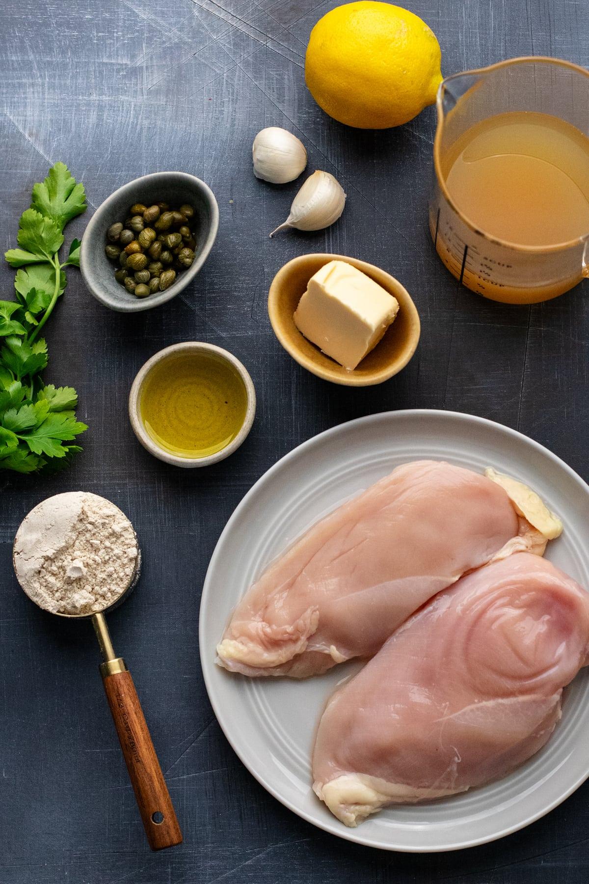 Ingredients for lemon chicken piccata arranged on dark gray background.