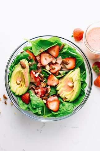 A bowl of strawberry spinach with avocado slices and chopped almonds.