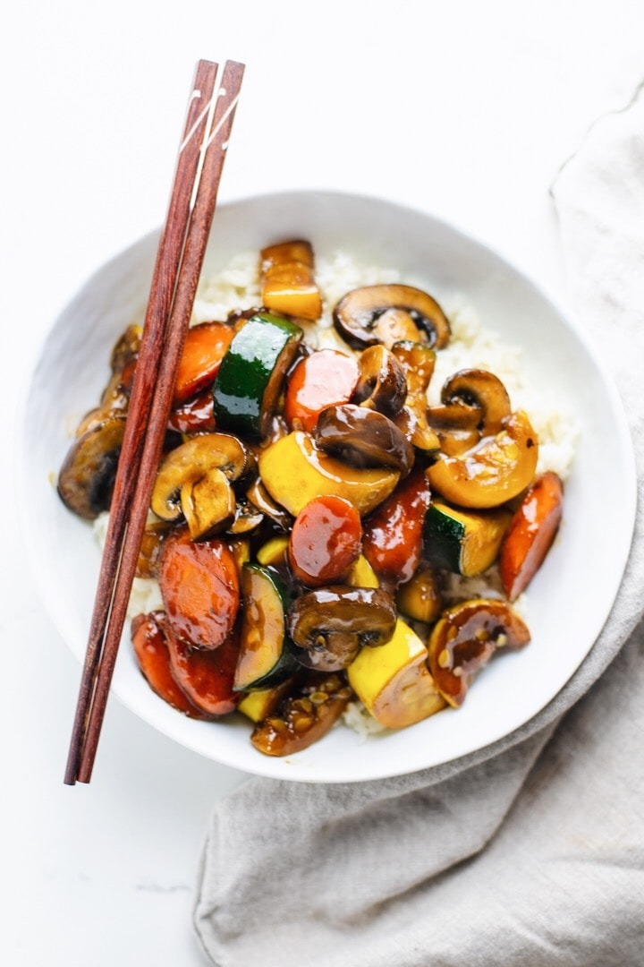 Zucchini stir fry in a white bowl with chop sticks.