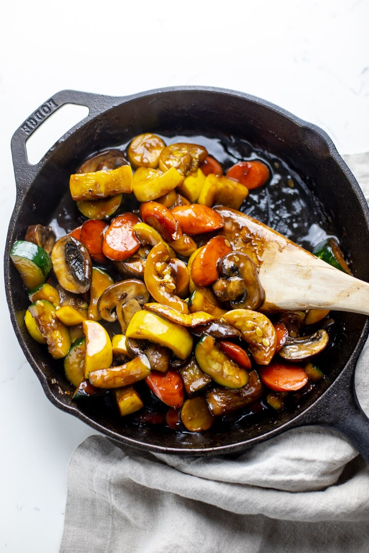 A black cast iron skillet with zucchini stir fry in it and a wooden spoon mixing it.
