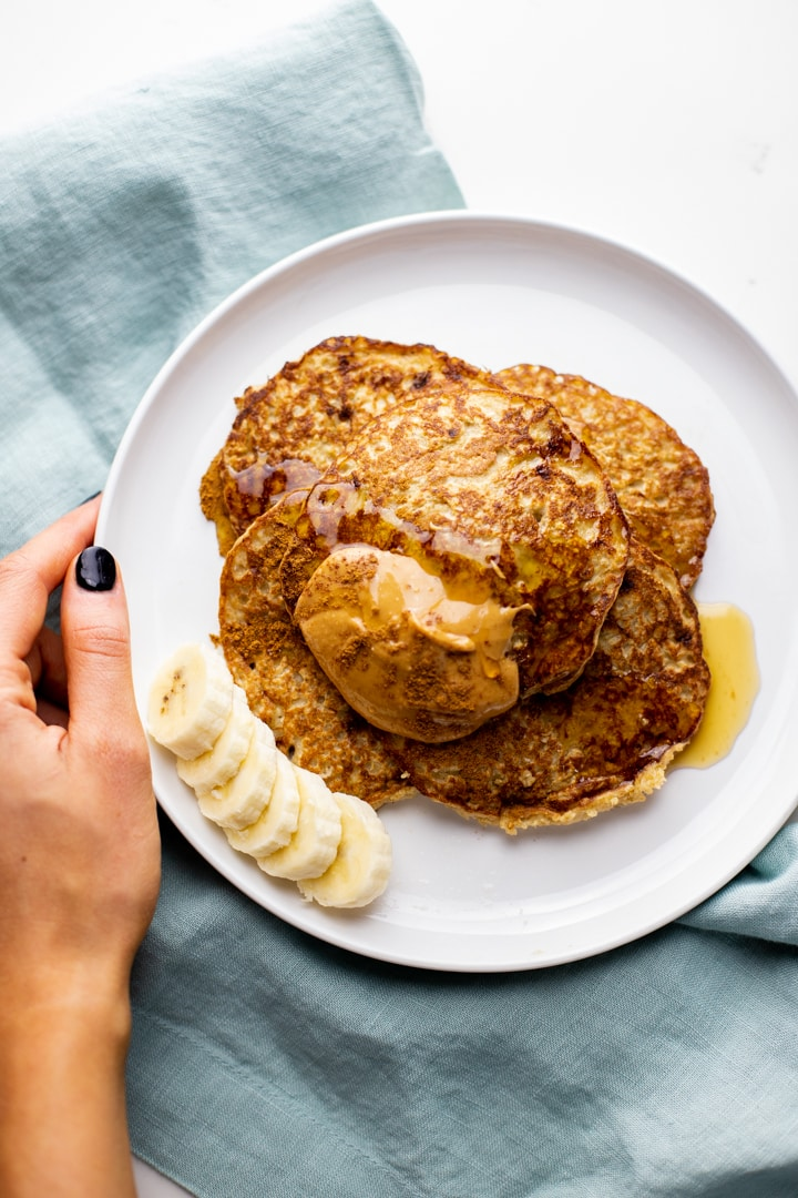 A hand holding a white plate with oatmeal banana pancakes over a blue napkin.