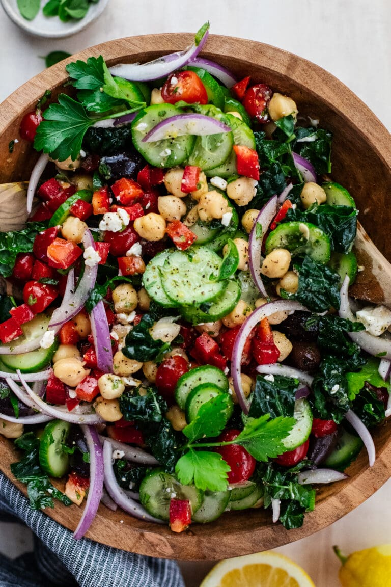 chopped vegetable salad in a wooden bowl with wooden spoons.