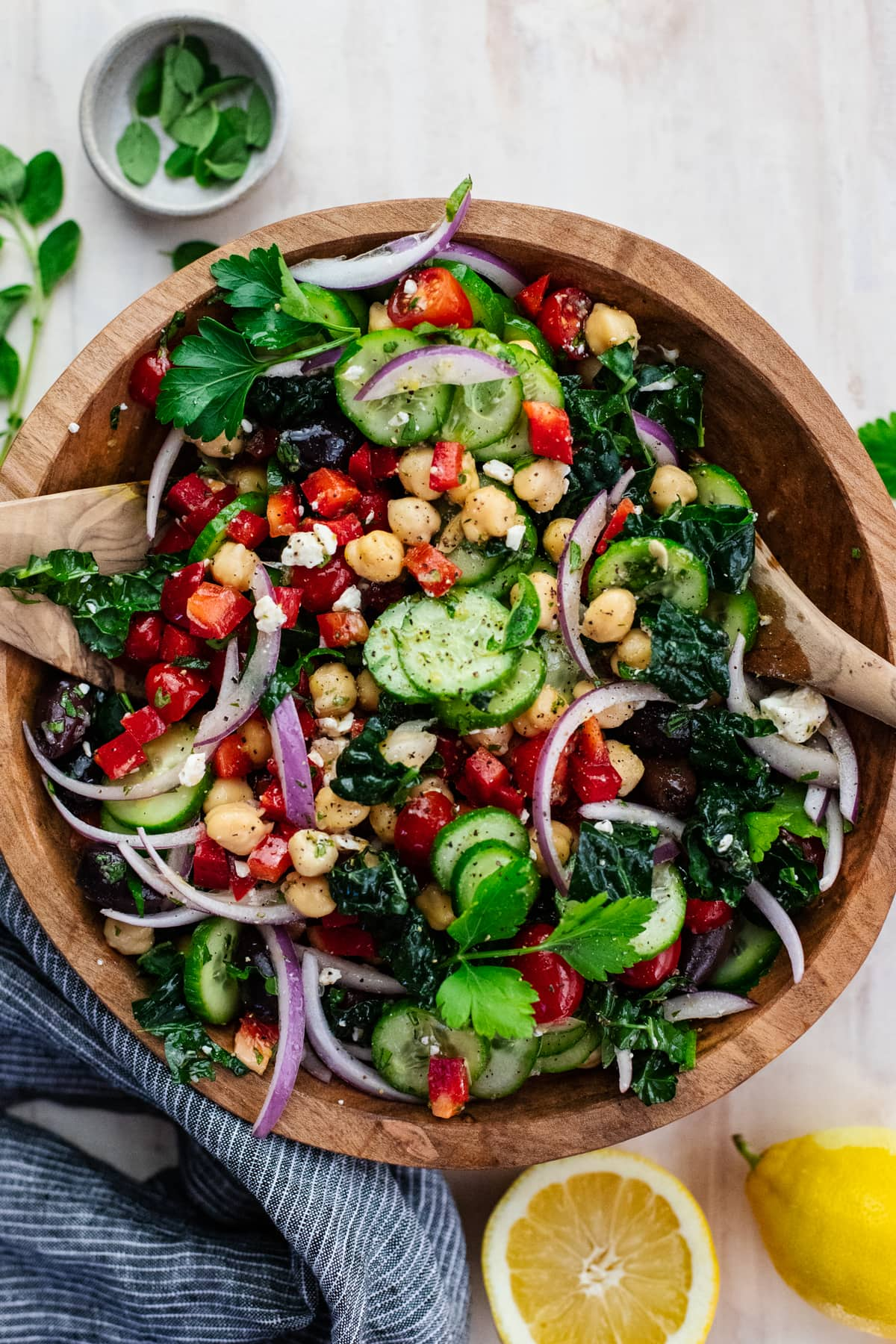 wooden bowl with chopped vegetables in a salad with wooden spoons on a light background with lemons and fresh herbs arranged around it.