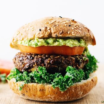 A close up of a black bean quinoa burger between a burger bun with a tomato slice, and guacamole on top.