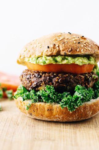 A close up of a black bean quinoa burger between a burger bun with a tomato slice, and guacamole on top.