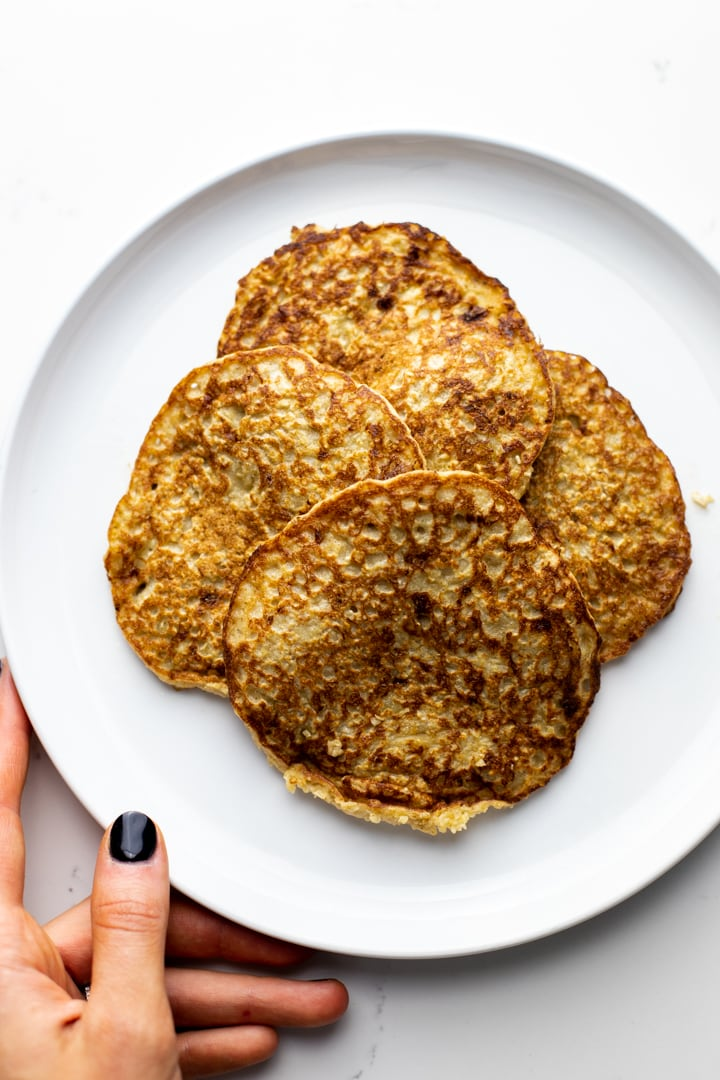 a hold holding a white plate with a stack of oatmeal banana pancakes.