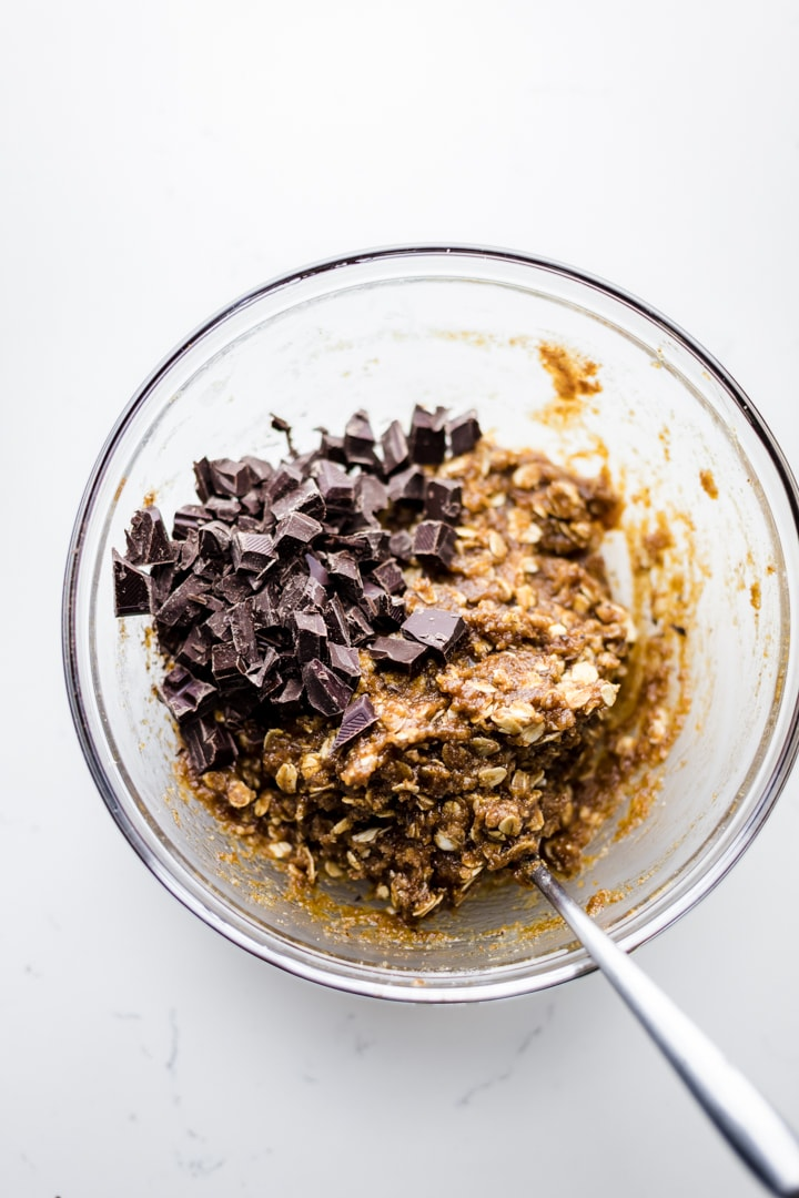A clear bowl with oatmeal chocolate chip cookie dough and chocolate chunks in it.