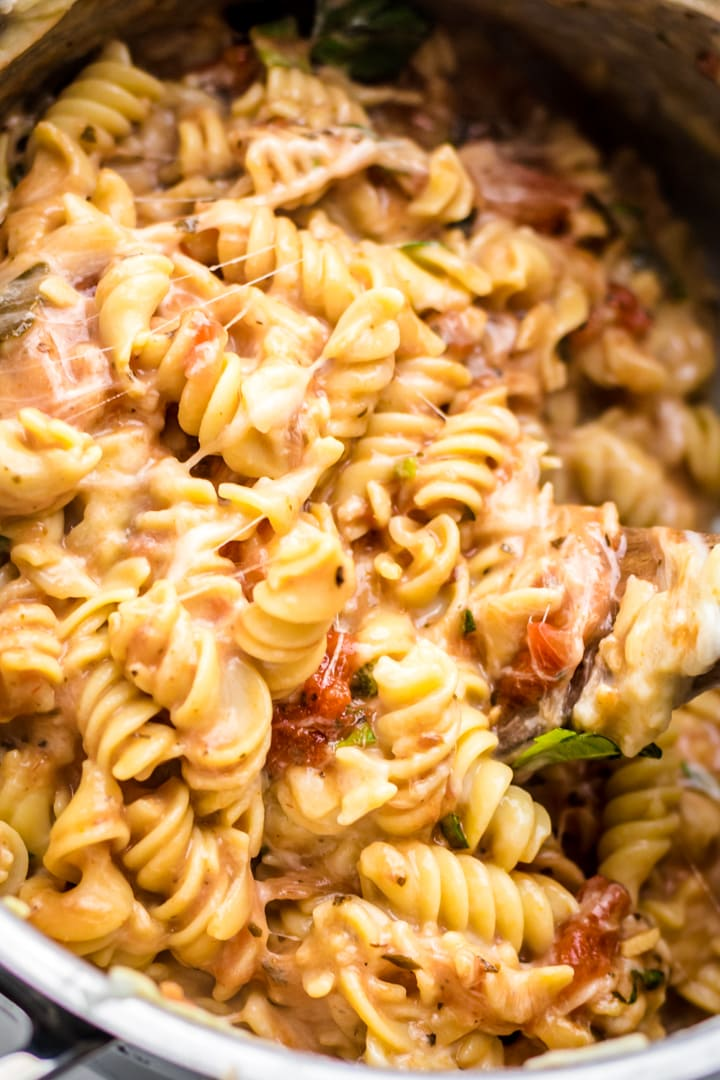 A close up of cheesy rotini pasta being stirred together in a pot.