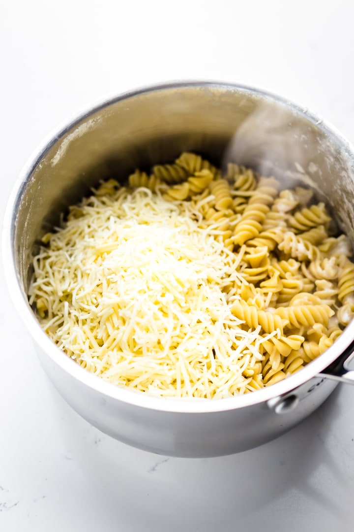 Cooked rotini pasta in a pot with cheese