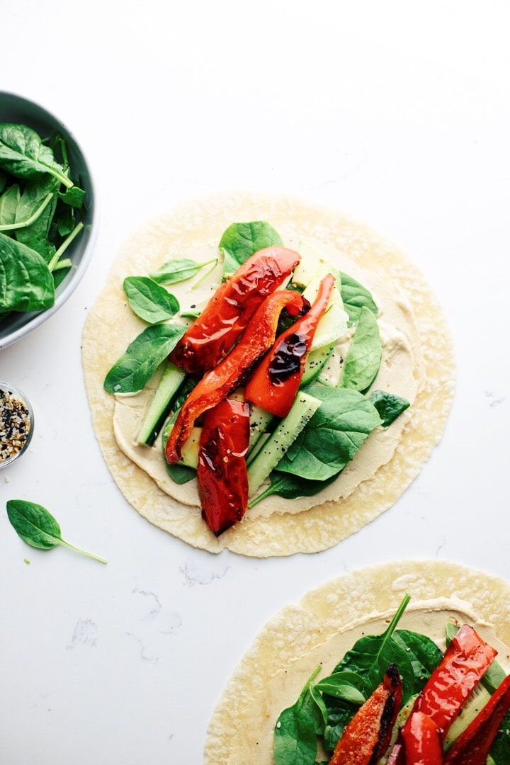 An open veggie wrap with spinach and roasted peppers with a bowl of spinach in the background.
